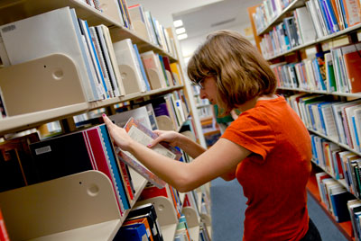 Young woman searches library book shelves.